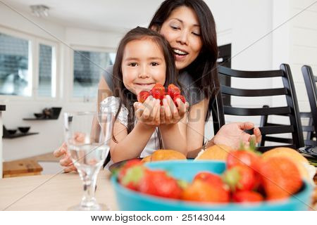 Mother and daughter sitting at table in kitchen with handful of strawberries