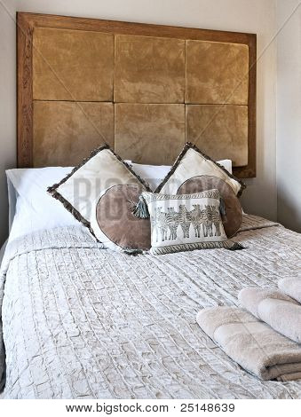 african folk style bedroom with brown leather header and zebra cushions