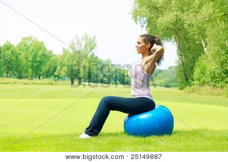 Fitness Women Exercising With Pilates Ball Outdoors