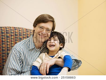 Father Holding Disabled Son In Doctor's Office
