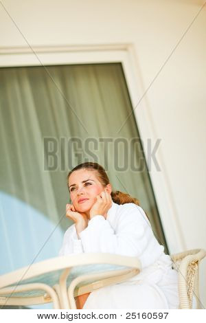 Dreaming Young Woman In Bathrobe Sitting At Table On Terrace