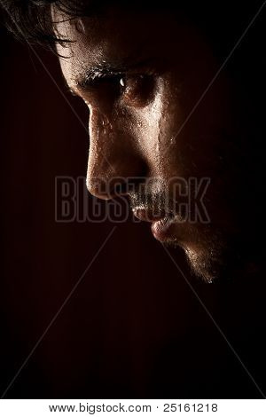 Young Indian angry man sweating over dark