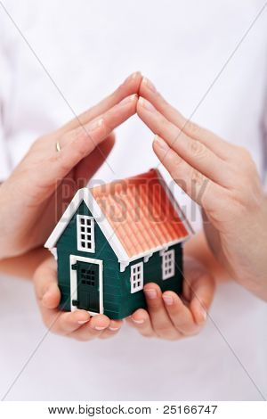 Protect your home - small house shielded with hands