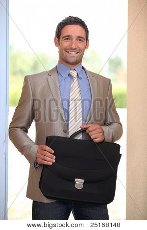 Businessman coming through a domestic doorway