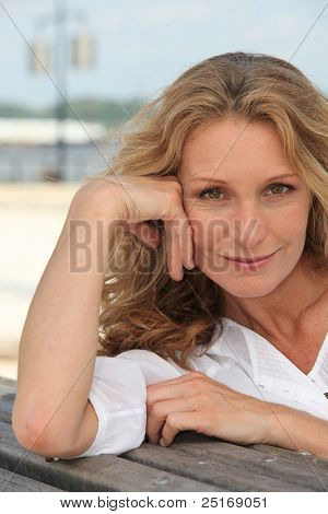 Blond woman sat on bench