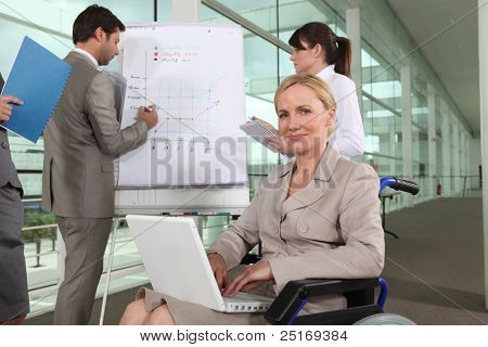 Businesswoman sitting in a wheelchair during a presentation