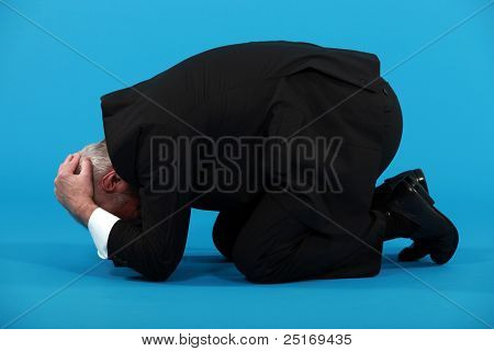 Businessman huddled on the floor