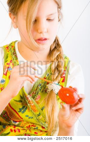 Young Girl Painting An Easter Egg Red