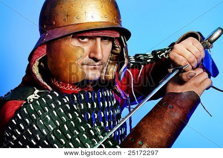 Portrait of a medieval male knight in armor over blue background.