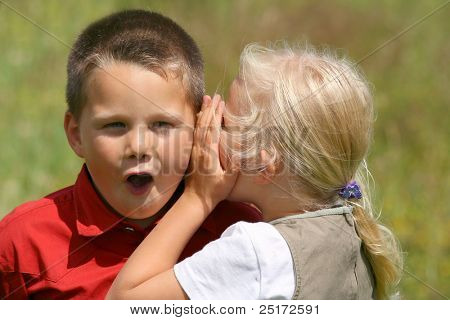 Girl whispering secret to a stunned boy
