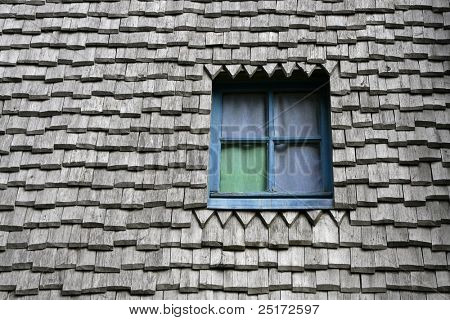 Colored window on a ancient wooden roof