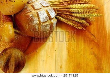 Assorted bread on wooden table with raw wheat background