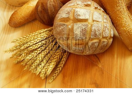 Assorted bread on wooden table with raw wheat