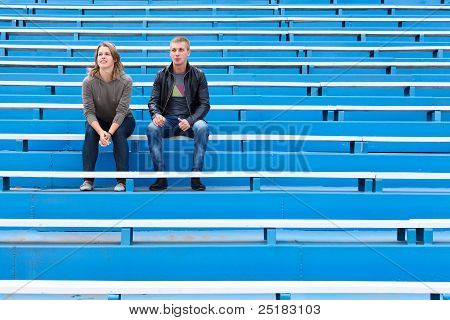 Man and woman sitting together on empty sports tribune