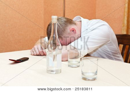 Drunken man laying on table with bottle of vodka