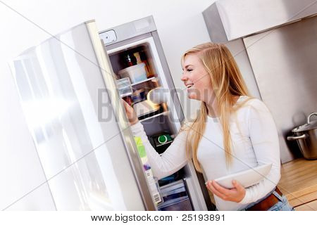 Woman cooking and getting something from the fridge