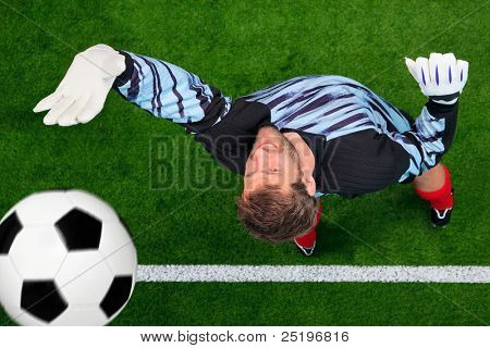 Overhead photo of a football goalkeeper missing saving the ball as it crosses over the line. Slight motion blur on the ball, focus is on his face.