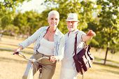 Try To Cycle There. Mindful Elderly Gentleman Pointing With His Index Finger While Helping His Wife  poster