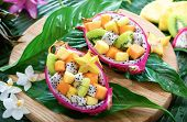 Exotic fruit salad served in half a dragon fruit on palm leaves with tropical flowers poster