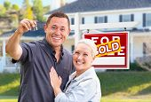 Young Adult Couple With House Keys In Front of Home and Sold For Sale Real Estate Sign. poster