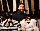 Guy With Happy Face Shows Fur Coats In Fashion Store. Shop Assistant Holds Grey Sable And Striped Ch poster