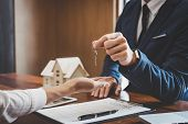 Real Estate Agent Sales Manager Holding Filing Keys To Customer After Signing Rental Lease Contract  poster