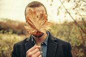 Seasonal autumn fashion. Portrait of a man covering his face with an autumn leaf. Autumn nature. poster