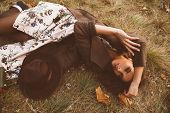 Autumn mood. Beautiful young woman lying on the autumn grass and yellow leaves. Seasonal autumn fash poster