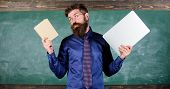 Stay Modern With Technology. Teacher Bearded Hipster Holds Book And Laptop. Modern Technologies Bene poster