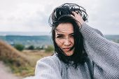 Happy And Funny Young Brunette Woman Taking Self Portrait And Posing Against Meadow And Overcast Sky poster