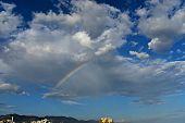 Bright Colorful Rainbow Over City, Sun Shining In Rainy Day, Beautiful Colors Phenomenon In Dark Blu poster