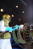 foto of sandblasting  - A worker sandblasting paint from a product - JPG