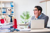 Businessman working with skeleton in office poster