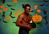 Guy With Blood On Face And Chest Demonstrates Biceps. Macho With Torso, Pumpkins And Bats Decoration poster