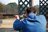 pic of shooting-range  - Man in blue jeans jacket takes aim with rifle - JPG