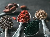 Spoons Of Various Superfoods On Black Wooden Table Background. Superfood Close Up As Chia Seeds, Spi poster