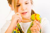 foto of easter-eggs  - Studio portrait of a young blond girl who is painting eggs for easter - JPG