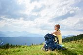 Back View Of Attractive Woman Tourist Resting On Grassy Hill With Backpack And Trekking Sticks. Fema poster