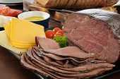 picture of sandwich  - Thin sliced roast beef with cheeses condiments and sliced rye bread for sandwiches - JPG
