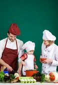 Child With Parents Cooking At Kitchen Table. Adorable Kid In Chef Hat. Happy Loving Family Preparing poster