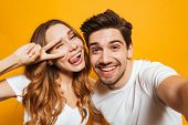 Portrait of smiling young couple man and woman taking selfie photo and showing peace sign isolated o poster