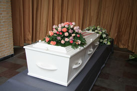 stock photo of funeral  - White casket covered with floral arrangements at a funeral service - JPG