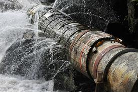 stock photo of leak  - A broken pipe that leaks water in all directions - JPG