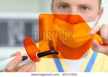 Dentist in mask holds ultraviolet curing light tool and looks at camera through orange glass. Focus on tool.
