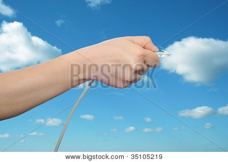 Concept or conceptual human or man hand holding a internet data cable in clouds over the blue sky, as a metaphor for plug, connection, technology, share, network, mobility, connectivity or communication