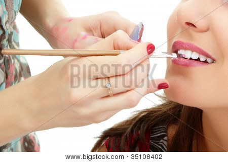 poster of esthetician apply lipstick on female lips closeup, isolated on white background