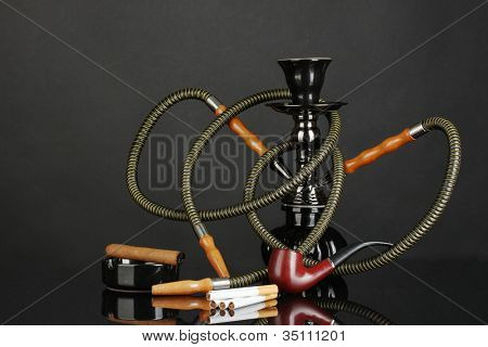 Smoking tools - a hookah, cigar, cigarette and pipe isolated on black background