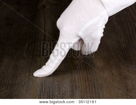 Female hand checking cleanliness on wooden background