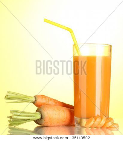 vaso de jugo de zanahoria sobre fondo amarillo