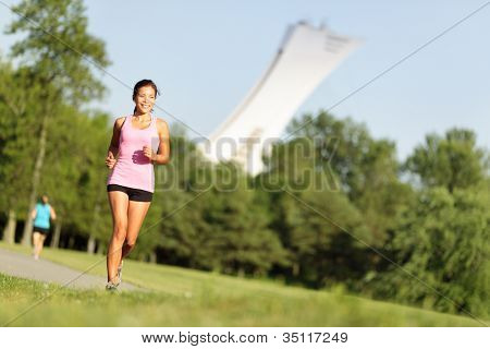 Running fitness in summer city park in Montreal, Quebec. Sport fitness woman running in park on summer day. Asian female runner during outdoor workout.